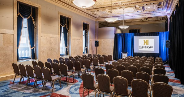 Hotel conference rooms with empty seats and high ceilings.